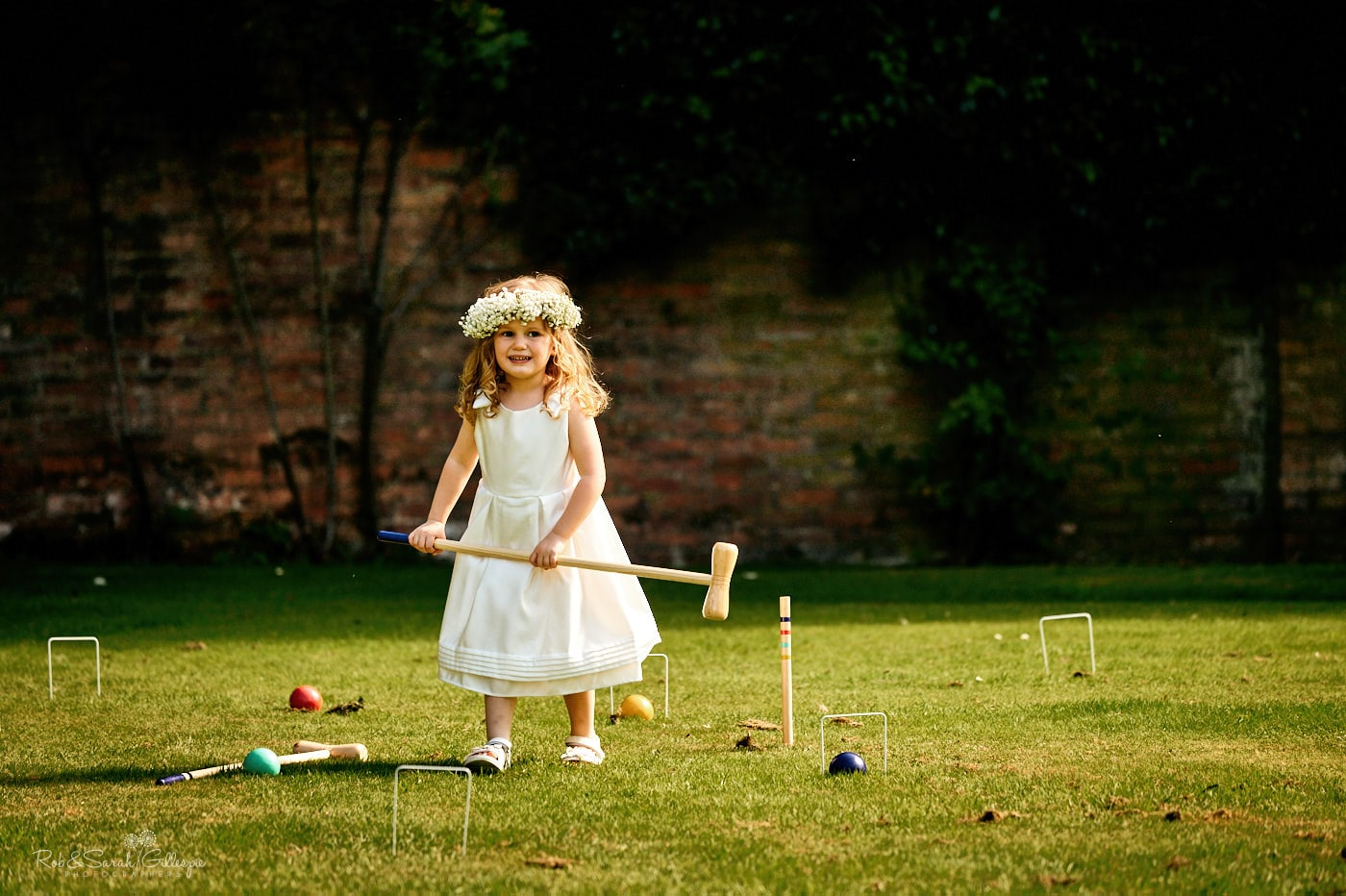 Flowergirl plays croquet during wedding reception