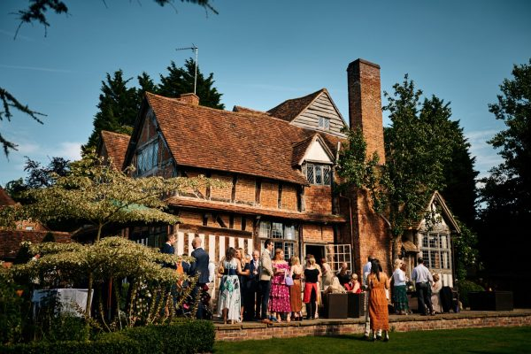 Gorcott Hall wedding venue in afternoon sunlight with guests relaxing outside