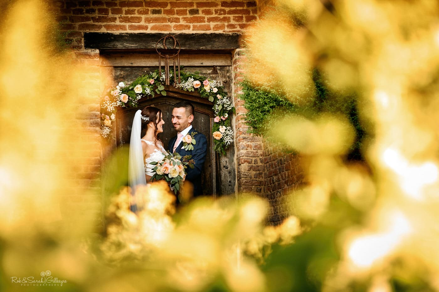 Bride and groom in doorway at Gorcott Hall surrounded by bright yellow flowers