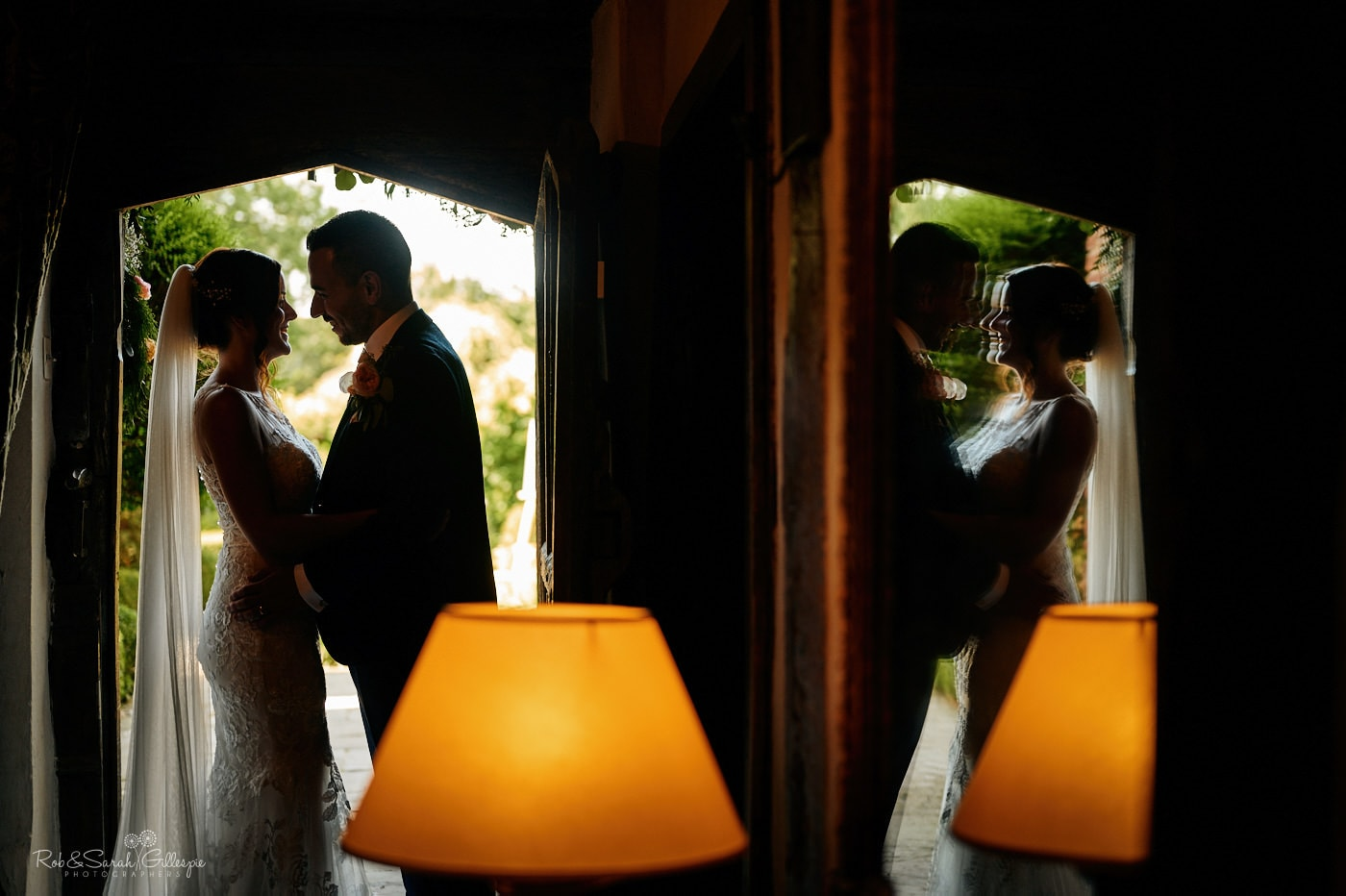 Bride and groom in doorway at Gorcott Hall, silhouetted by afternoon sun