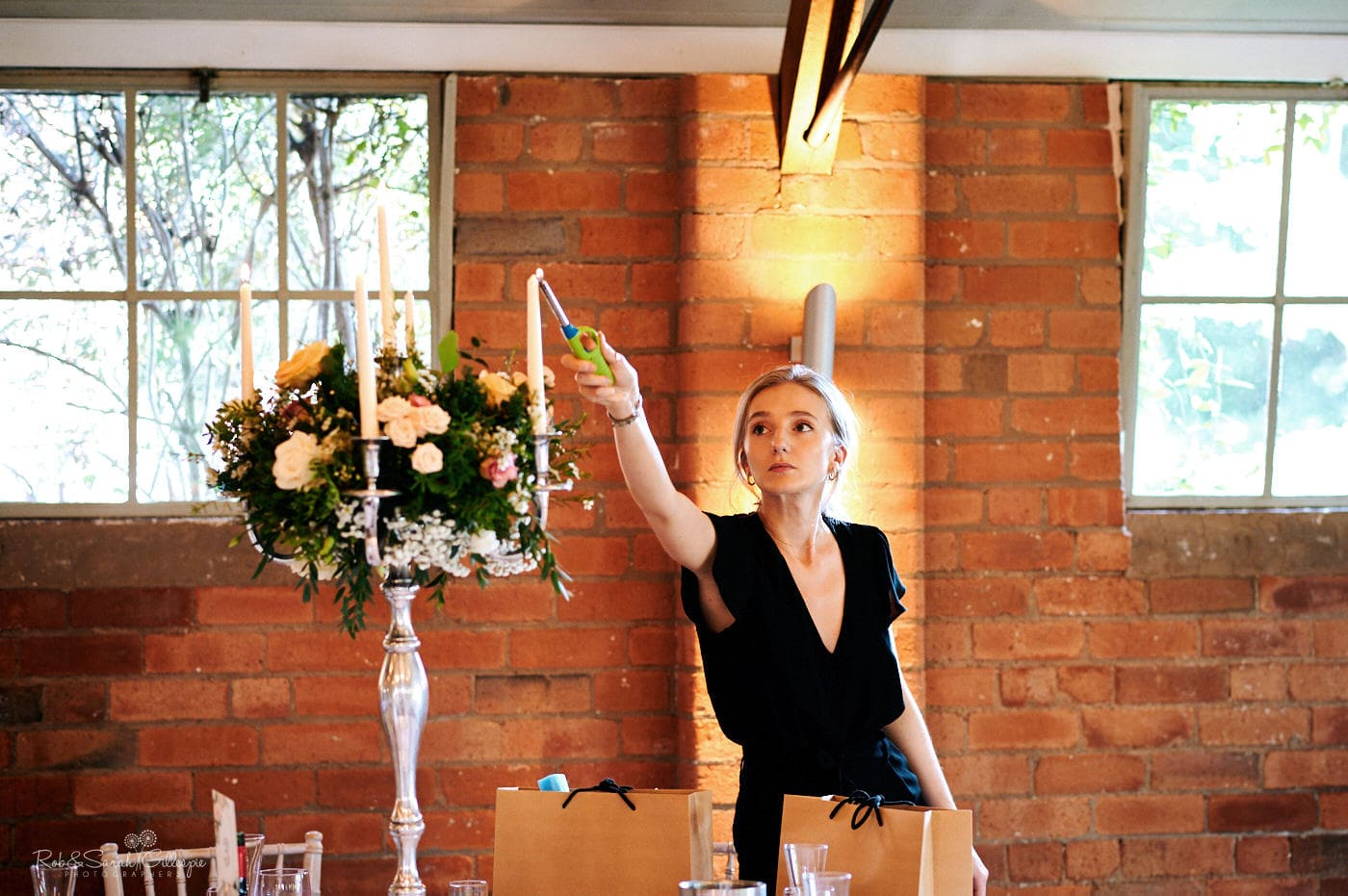 Member of staff lights candles for wedding meal