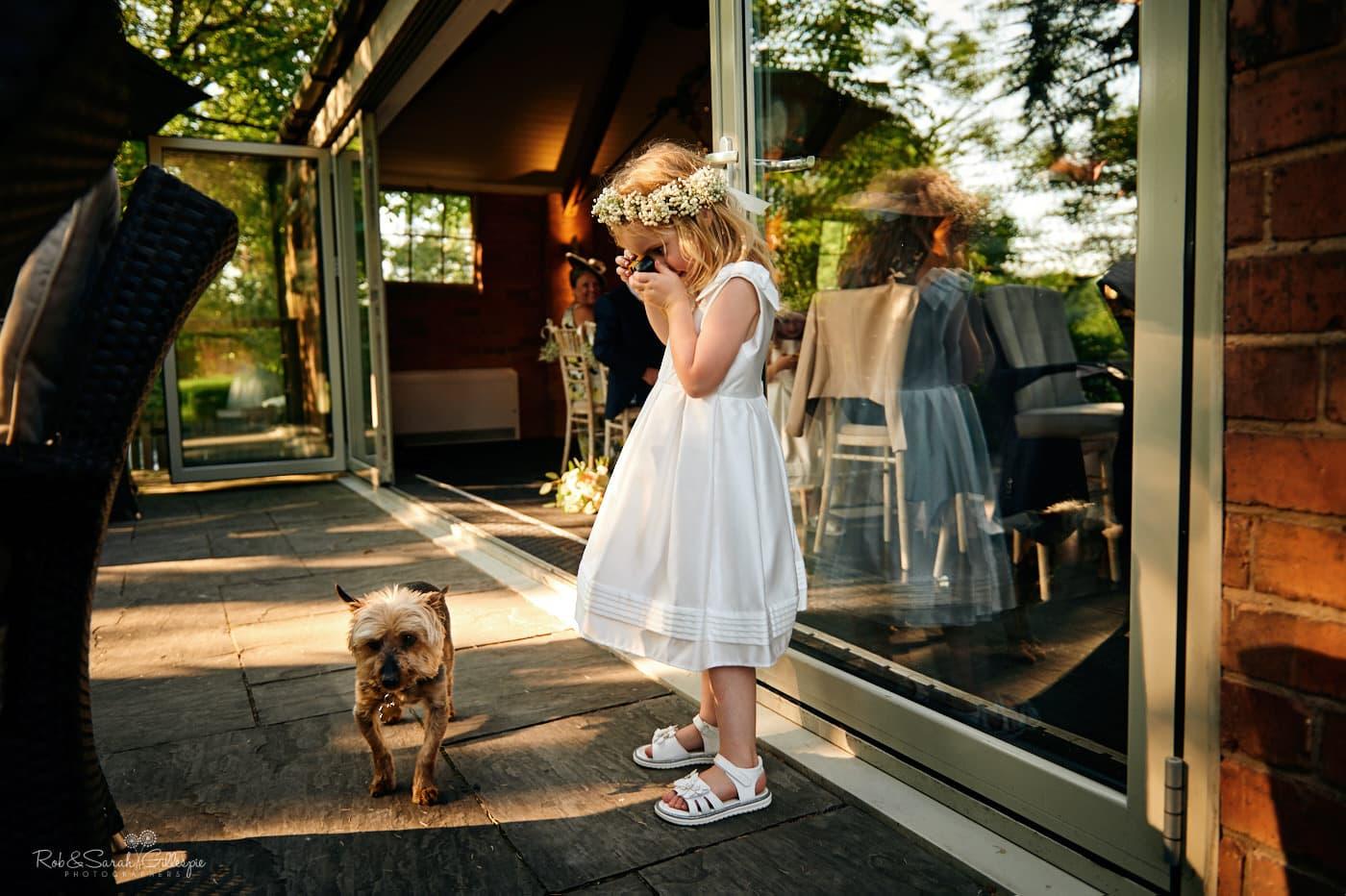 Flowergirl takes photo of cute dog at Gorcott Hall wedding