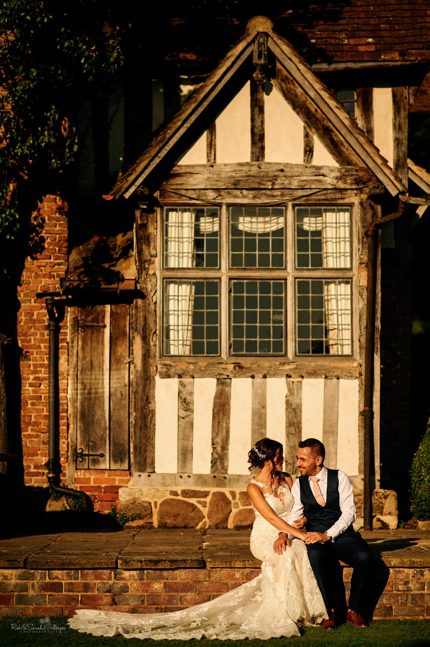 Bride and groom sitting in sunlight at Gorcott Hall