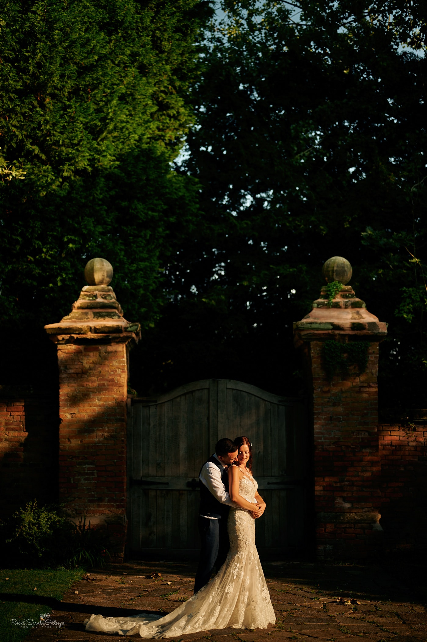 Bride and groom in grounds at Gorcott Hall in bright afternoon sunlight