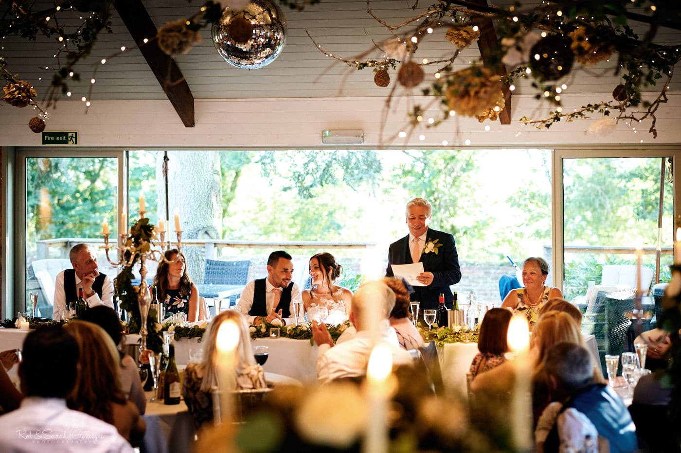 Bride's dad gives wedding speeches as guests listen