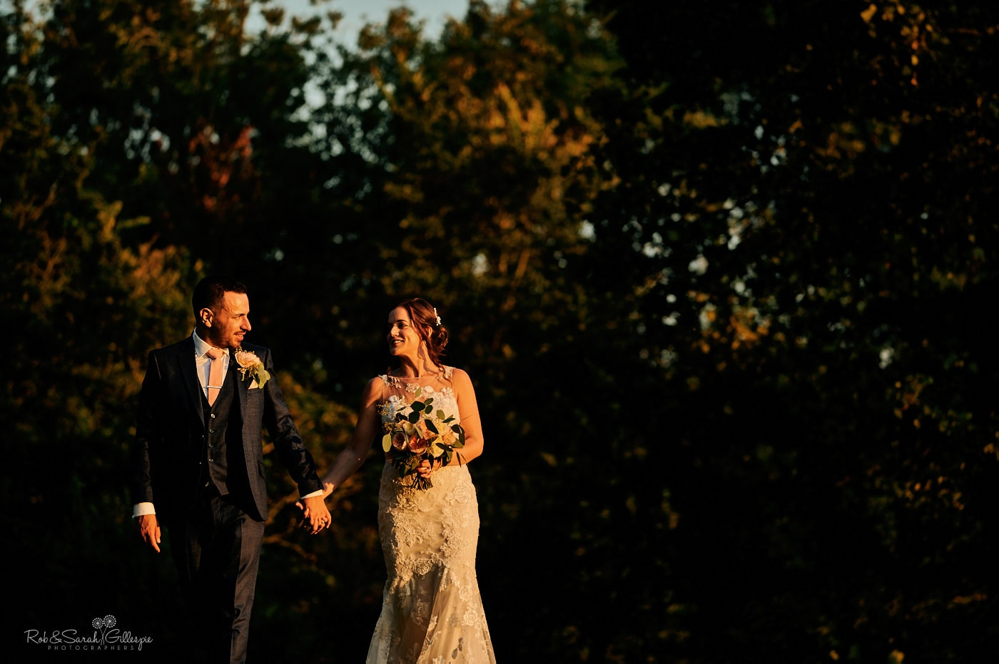 Bride and groom walk through gardens at Gorcott Hall on a beautiful summer evening