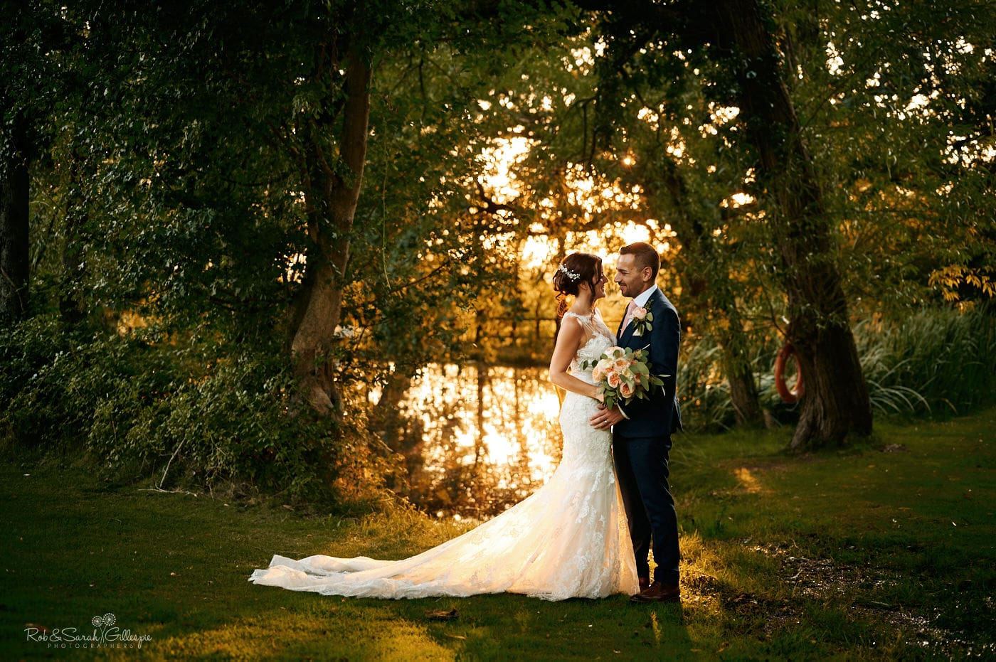 Newly married couple in gardens at Gorcott Hall with sunlit pond in background