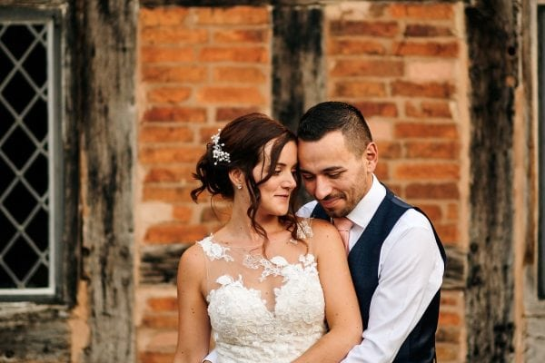 Bride and groom cuddled together in front of beautiful building