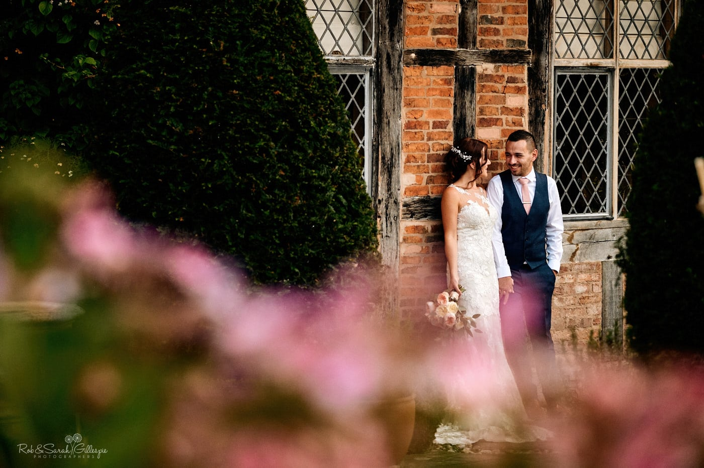 Bride and groom talking while leaning against old wall at Gorcott Hall