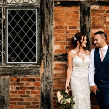 Bride & Groom leaning against old brick wall at Gorcott Hall