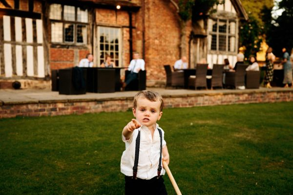 Young boy pointing at camera during wedding