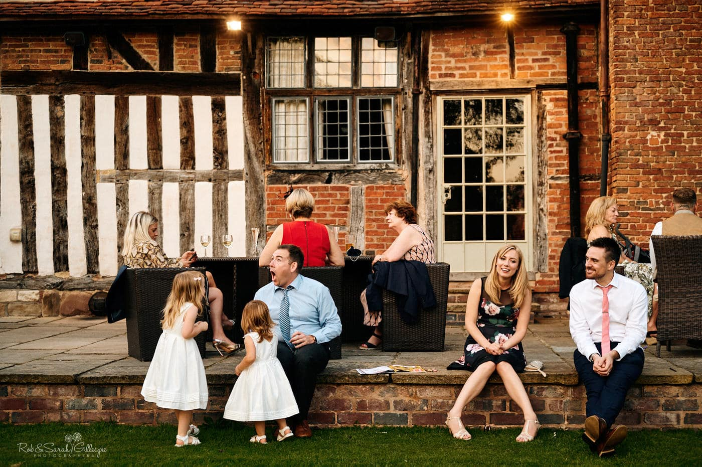Wedding guests sitting on stone step at Gorcott Hall