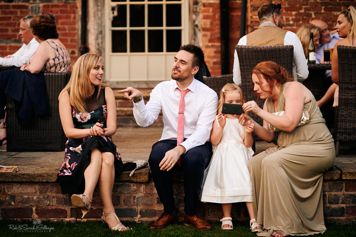 Wedding guests chatting and relaxing at Gorcott Hall wedding in evening light