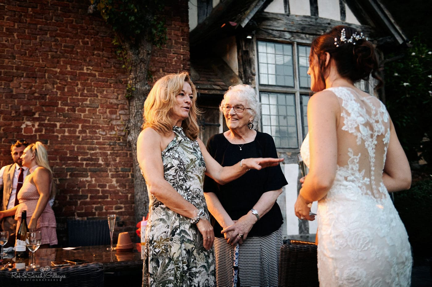 Wedding guests chat to bride during evening reception