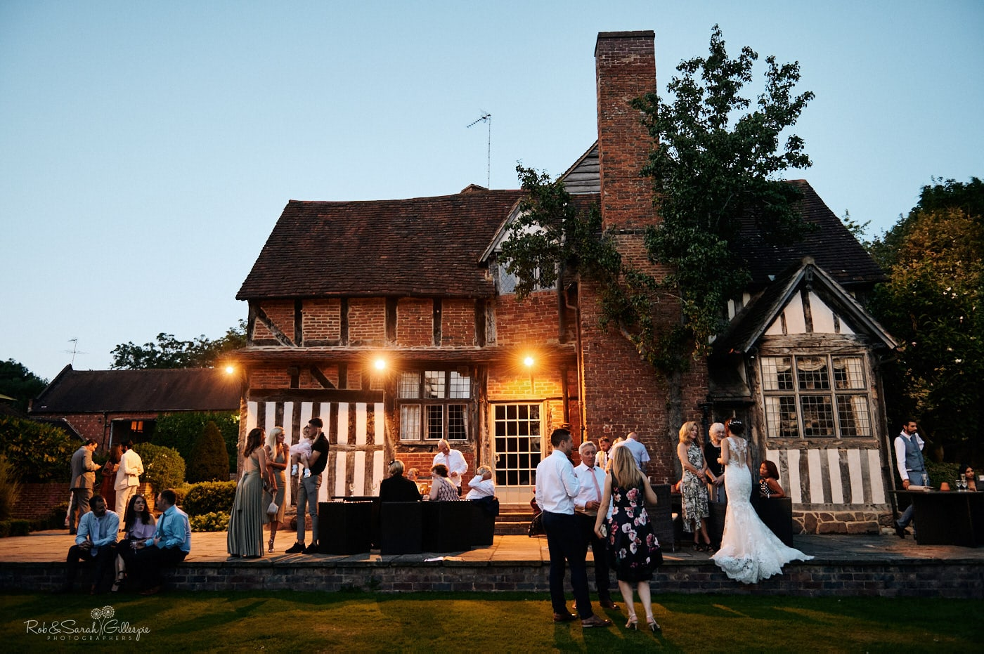 Exterior of Gorcott Hall during summer evening with wedding guests chatting and relaxing