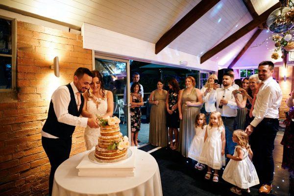 Bride and groom cut wedding cake as guests watch