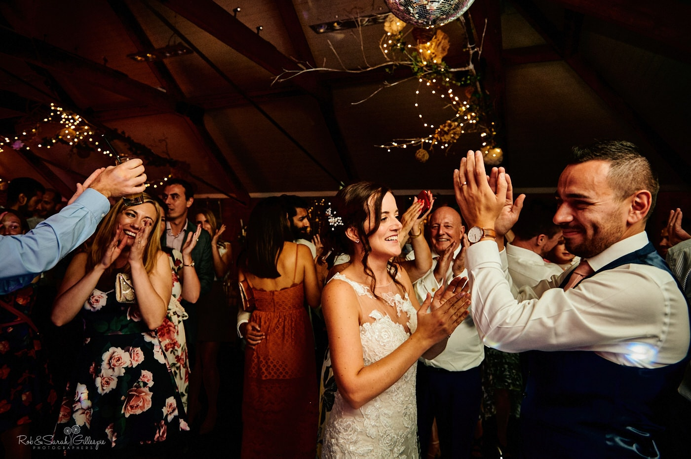 Wedding guests clap for live band during party