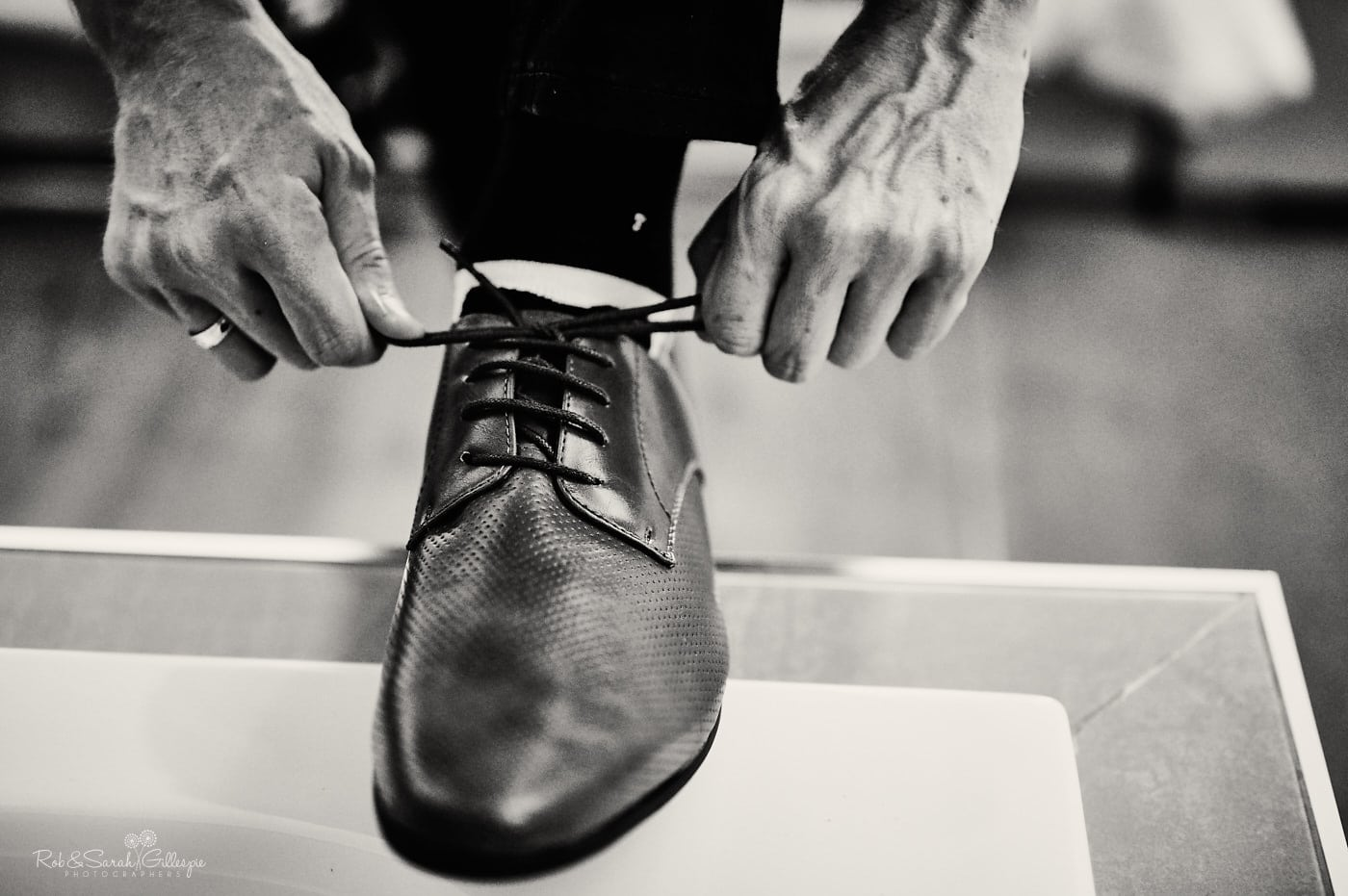 Groom ties shoelaces before wedding