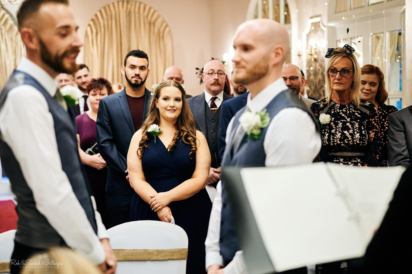 Wedding guests watch as two grooms get married