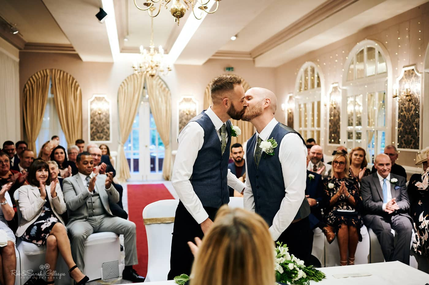 Two grooms kiss during wedding ceremony at Moor Hall Hotel