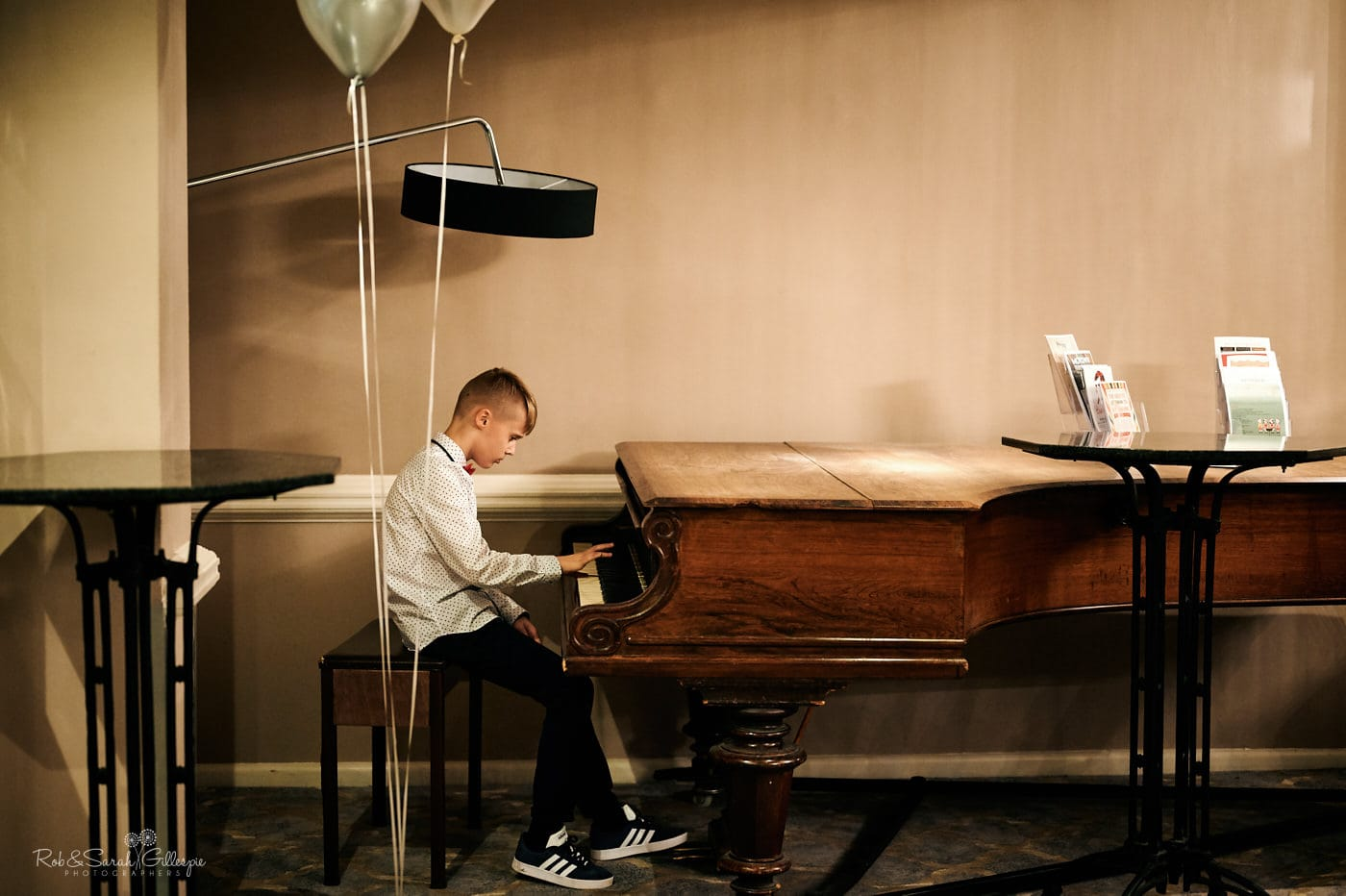 Young wedding guest plays piano at reception