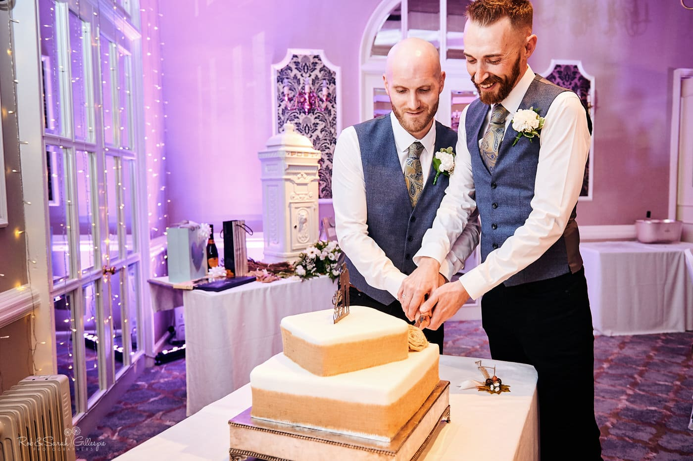 Two grooms cut wedding cake at Moor Hall Hotel same-sex wedding