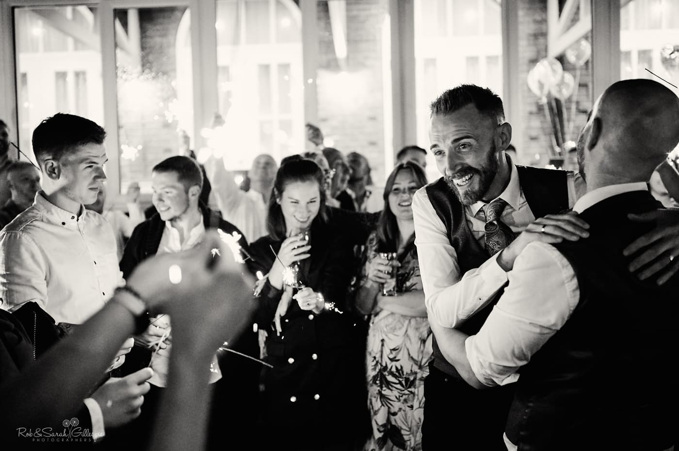 Two grooms surrounded by wedding guests with sparklers at Moor Hall Hotel