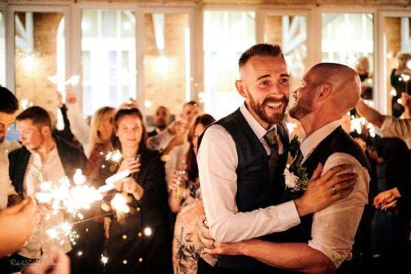 Two grooms surrounded by sparklers on their wedding day