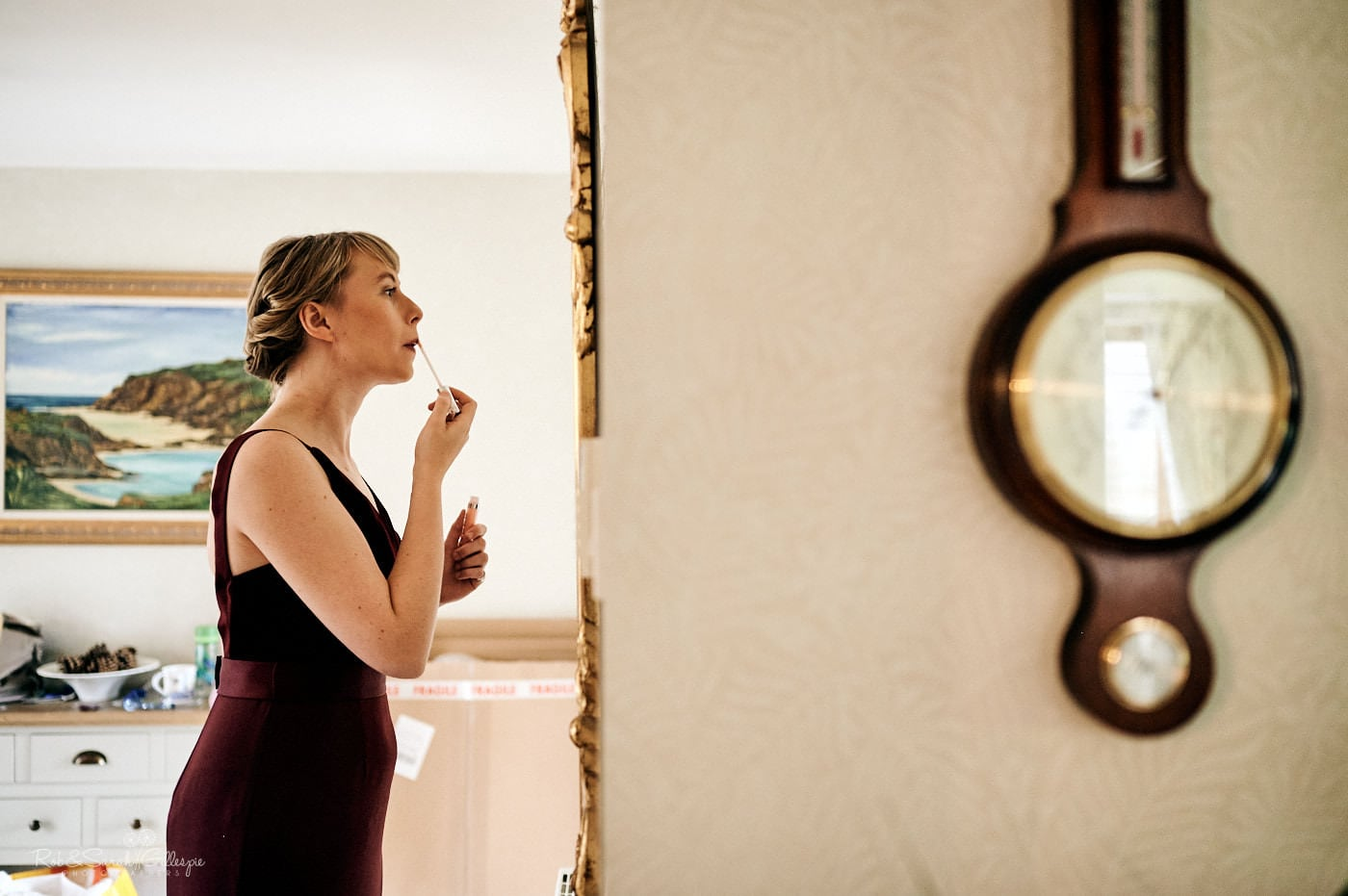 Bridemaid applies lipstick in mirror