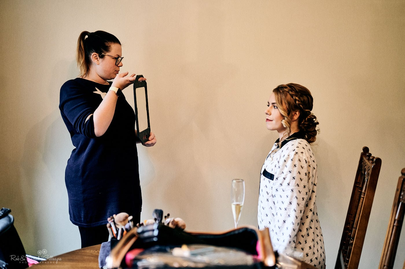 Hair stylist shows bride her hair in a mirror