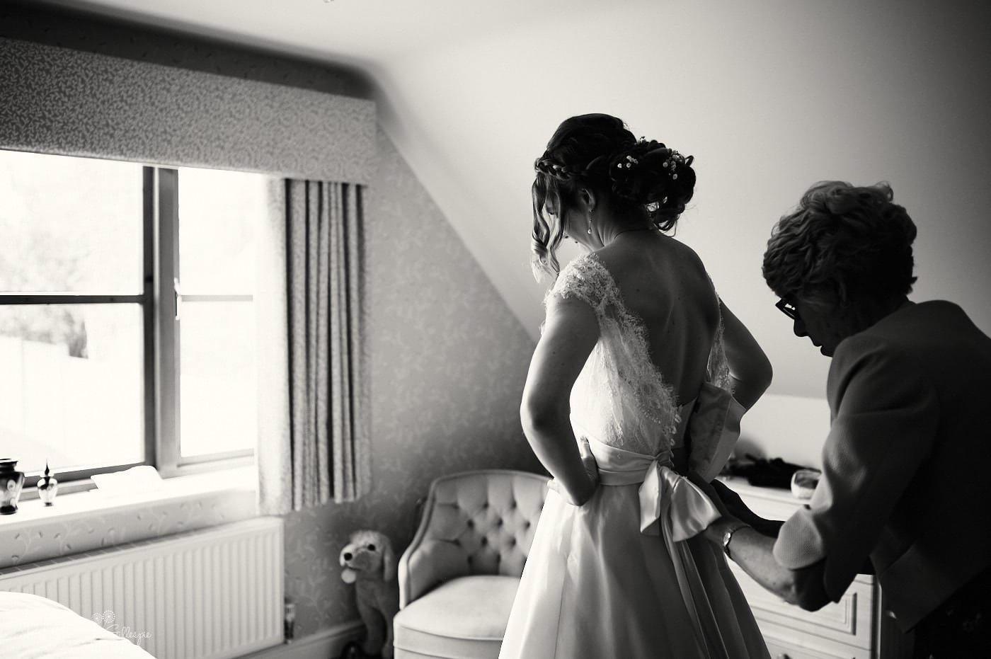 Bride has dress fastened by mum before wedding