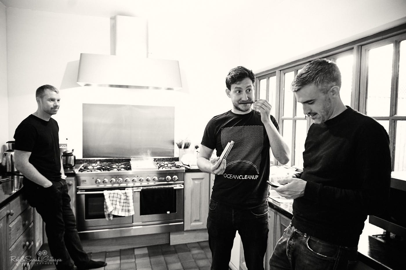 Groomsmen larking about in kitchen before breakfast