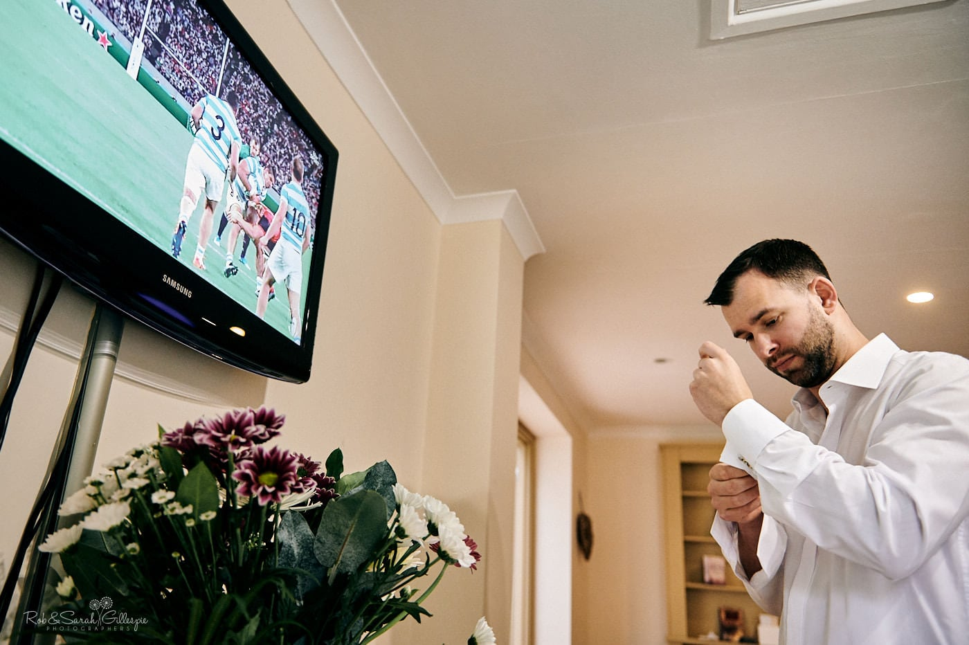Groom prepares for wedding while watching rugby match on TV