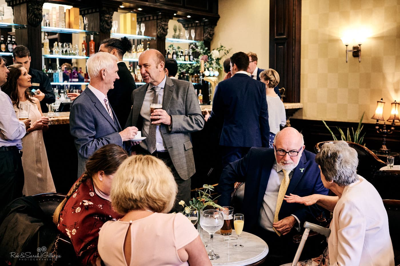 Wedding guests chat in bar at Spring Grove House