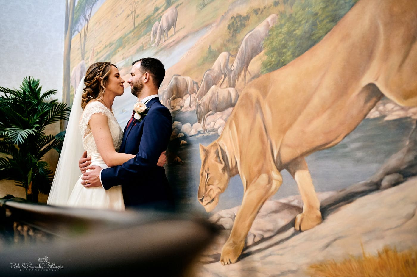 Wedding couple in front of large mural feautirng wild animals at Spring Grove House