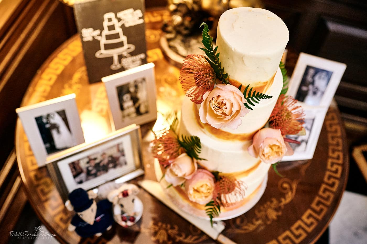 Beautiful wedding cake with white and orange icing, decorated with flowers and surrounded by old wedding photos of relatives