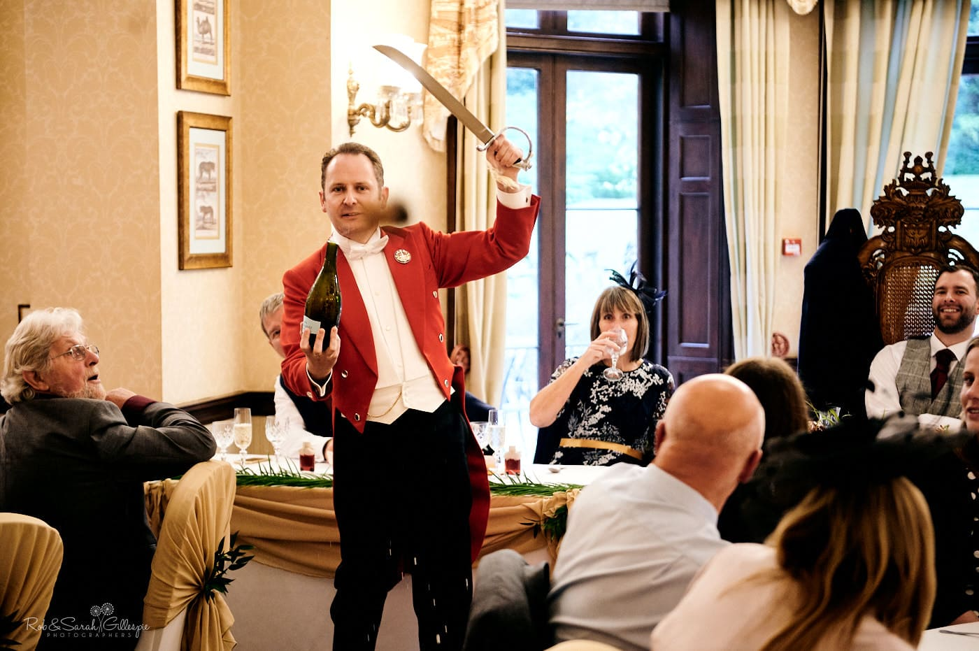Wedding master of ceremonies performs sabrage with sword and champagne bottle