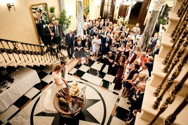 Bride and groom cut wedding cake at Spring Grove House as wedding guests watch