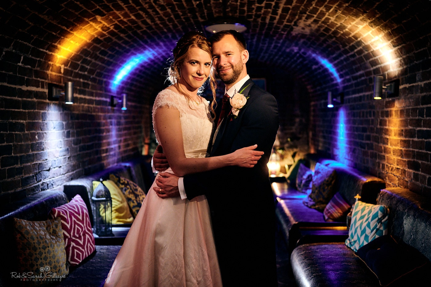 Bride and groom un cellar at Spring Grove House surrounded by sofas and lighting