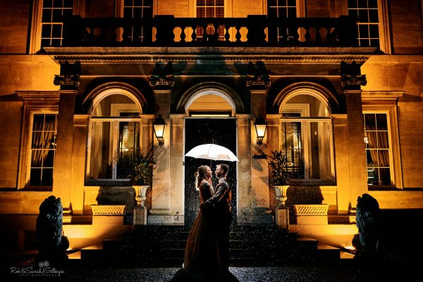 Bride and groom outside Spring Grove House at night holding umbrella in rain