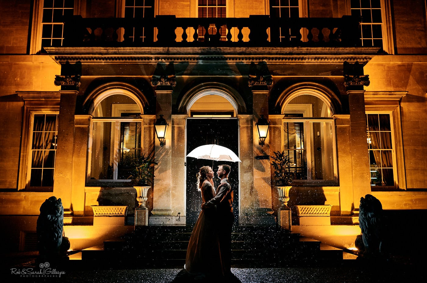 Bride and groom under umbrella outside Spring Grove House at night