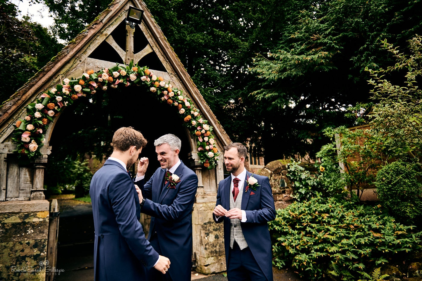 Groom and groomsmen fixing buttonhole flowers in front of lychgate at St Peter's church Pedmore