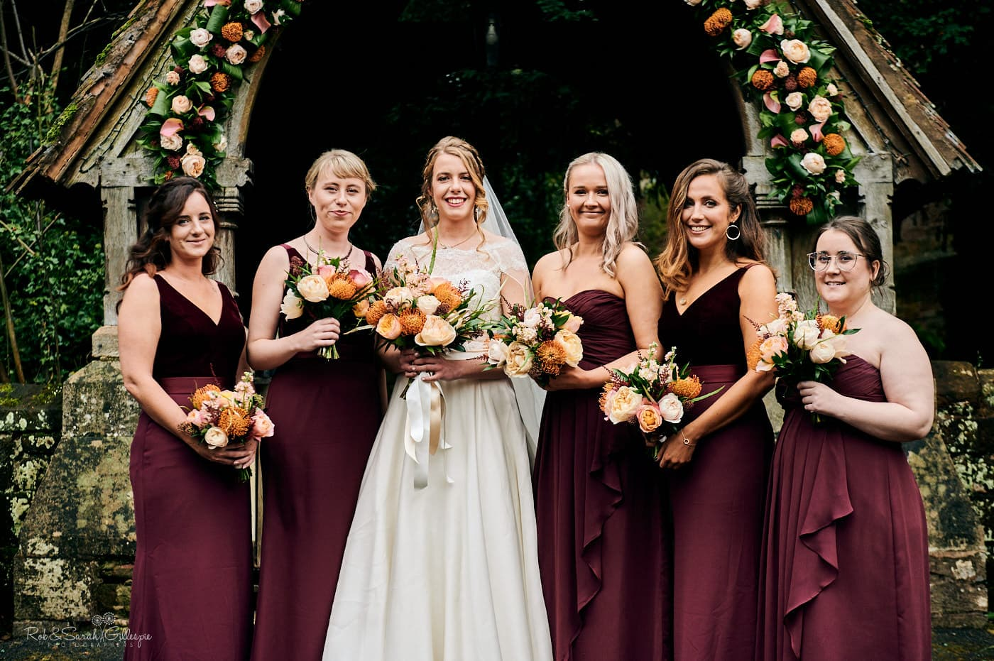 Group photo of bride and bridesmaids in front of lychgate at St Peter's church Pedmore
