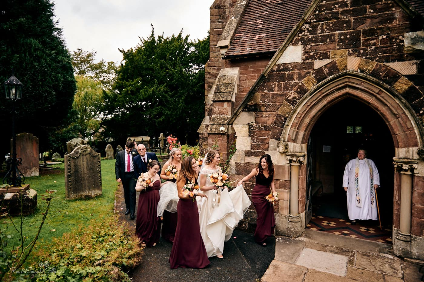 Bride and bridesmaids walk to church entrance for wedding service with vicar waiting in doorway