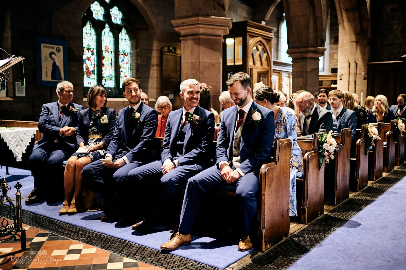 Groom waits for bride at front of church with friends and family around him