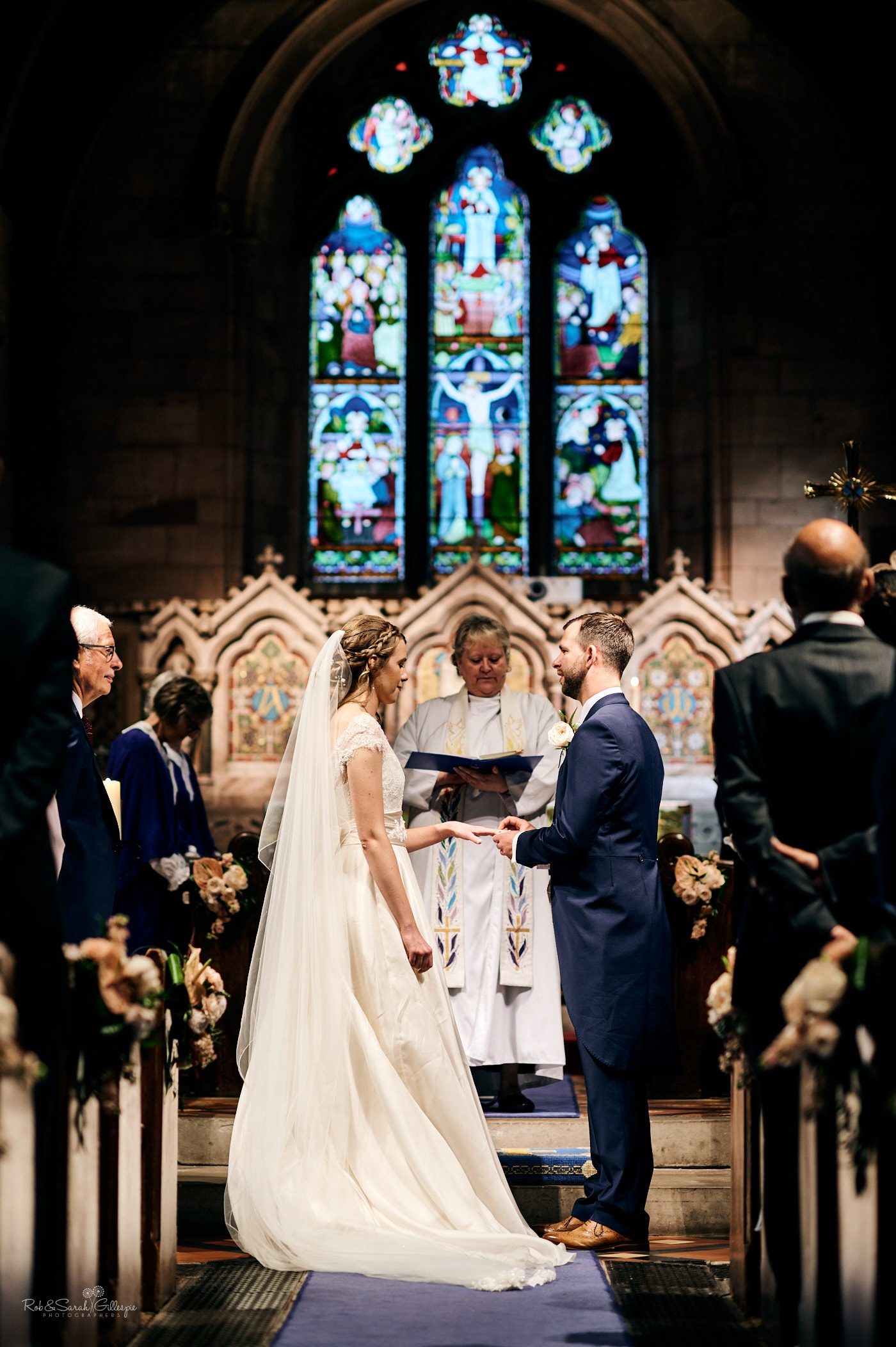 Bride and groom exchange rings during wedding at St Peter's church Pedmore