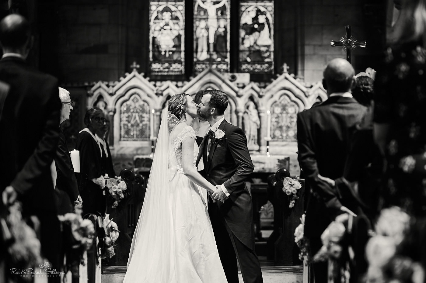 Bride and groom first kiss during church wedding ceremony