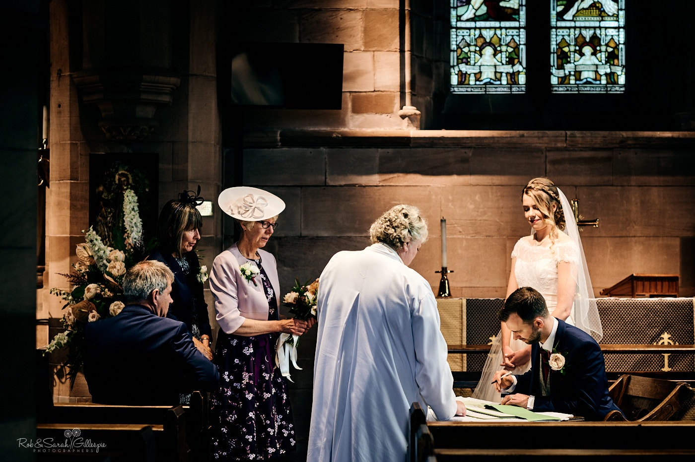Bride and groom sign marriage register during church service at St Peter's Pedmore