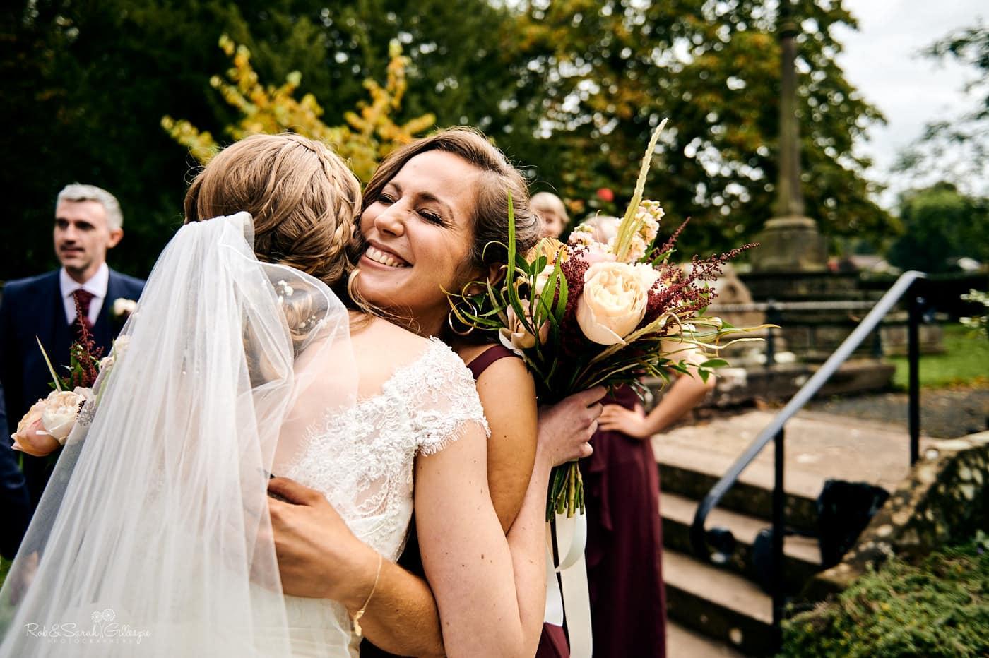 Wedding guests hug bride after wedding ceremony