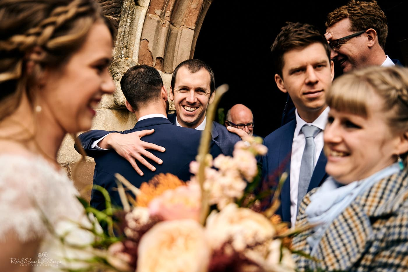 Wedding guests congratulate bride and groom after church wedding